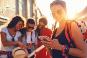 Lächelndes Mädchen mit Sonnenbrille und Smartphone in der Hand, im Hintergrund betrachten drei Menschen das Display eines Smartphones.