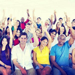 Gruppe unterschiedlicher Menschen, die ihre Hand in die Luft strecken.